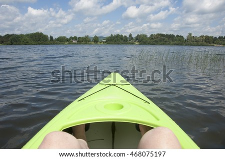 Sitting in a neon green kayak looking across the lake at the other side.  Point of view.  Lac de Source in Mont Laurier, Quebec, Canada.