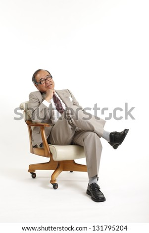 Sitting isolated on white background full body Asian senior businessman