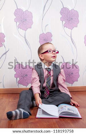 Sitting little boy with diary looks like a business man - stock photo