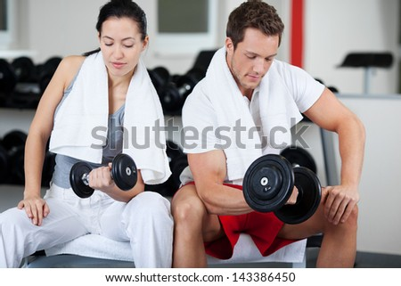 Sitting man and woman lifting dumbbell in gym - stock photo