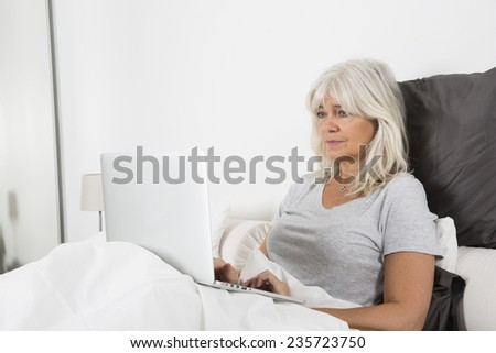 Sitting Mid Age woman with a laptop in bed - stock photo