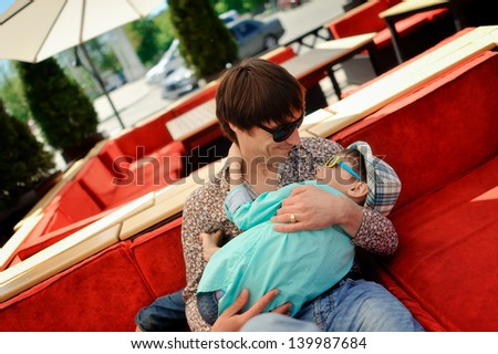 sitting on a red couch and dad holding his son in the Hat - stock photo
