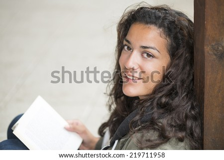 Sitting on street, a young woman (20s) with a book on knees looking at camera. She is relaxed and smiling. Closeup and  and copy space - stock photo