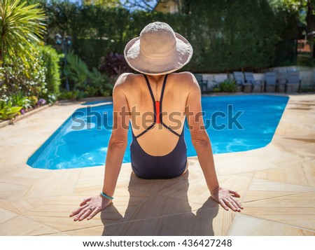 Sitting on the edge of the pool on a hot summers day relaxing wearing a sun hat.  - stock photo