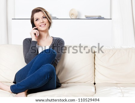 Sitting on the sofa pretty woman speaks on the phone - stock photo