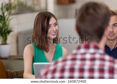 Sitting Pretty Young Woman Wearing Green Sleeveless Outfit Talking to Friends at the Table. - stock photo