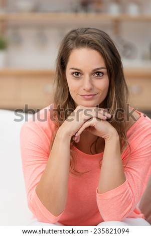 Sitting Pretty Young Woman with Long Blond Hair, Wearing Casual Pink Shirt, Putting her Both Hands Under her Chin While Looking at the Camera. - stock photo