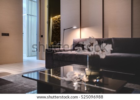 Sitting-room in a modern style with the wooden walls and a parquet with a carpet on the floor. There is a black marble table with flowers, sofa with pillows, mirror, entrance to the bathroom, lamp.
