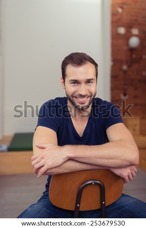 Sitting Smiling Handsome Man Wearing Casual Clothing, Looking at Camera with Crossed Arms. - stock photo
