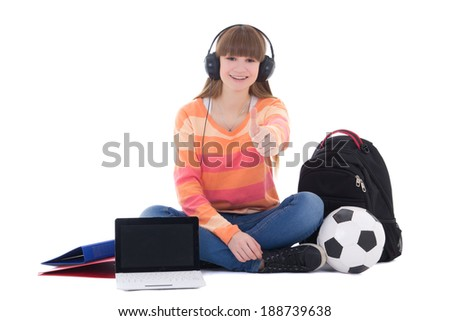 sitting teenage girl listening music in headphones with laptop isolated on white - stock photo