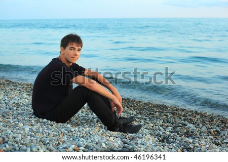 sitting teenager boy on stone seacoast near sea - stock photo