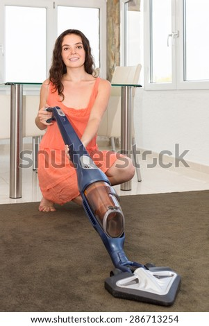 sitting woman in gown cleaning with a vacuum cleaner