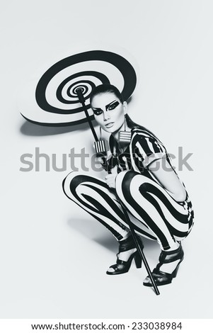 sitting woman in striped costume with umbrella - stock photo