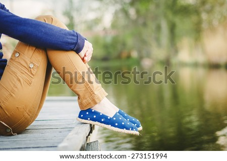 Sitting Woman's feet in a sneakers near the lake - stock photo