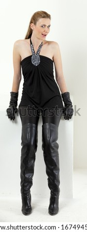sitting woman wearing black clothes and black boots - stock photo