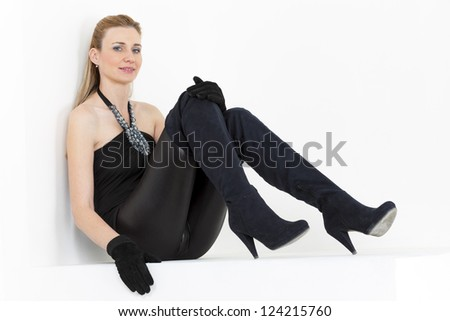 sitting woman wearing black clothes and boots - stock photo