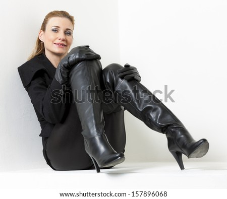 sitting woman wearing black clothes and boots