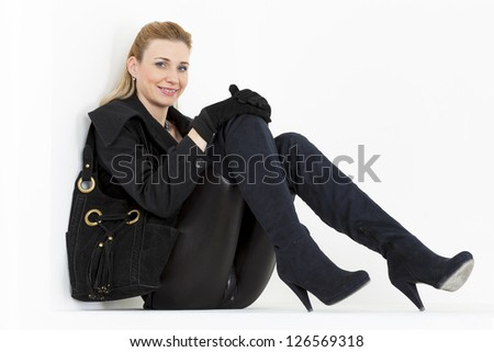 sitting woman wearing black clothes and boots with a handbag - stock photo