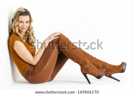 sitting woman wearing brown clothes and boots - stock photo