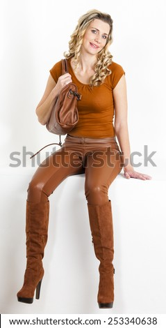 sitting woman wearing brown clothes and boots with a handbag