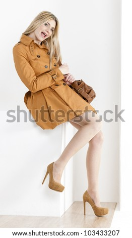 sitting woman wearing brown coat and pumps with a handbag