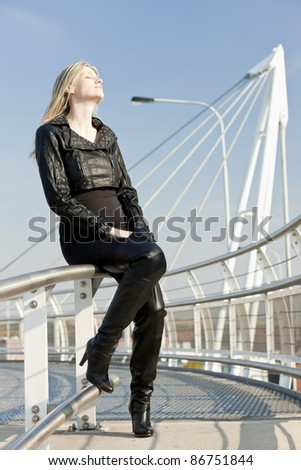 sitting woman wearing fashionable black boots