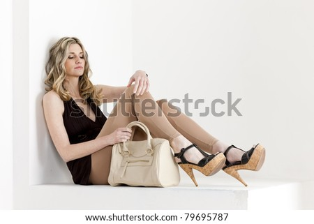 sitting woman wearing summer clothes and shoes with a handbag - stock photo