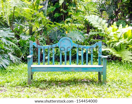 sitting wooden vintage bench in the tropical garden