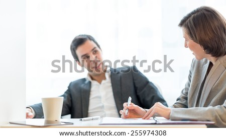 Sitting Young Business People Discussing Business Matters Inside the Office. Focus on the female partners face. - stock photo