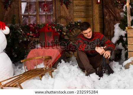 Sitting Young Handsome Man Holding Ice Skates with Serious Facial Expression, Surrounded by Beautiful Christmas Decors. - stock photo