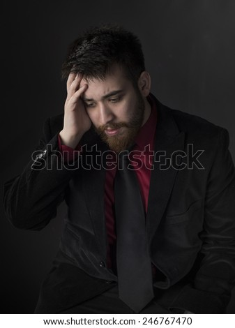 Sitting Young Man in Black and Maroon Formal Attire Suffering Headache with Hand on his Head. Captured on Gray Background - stock photo