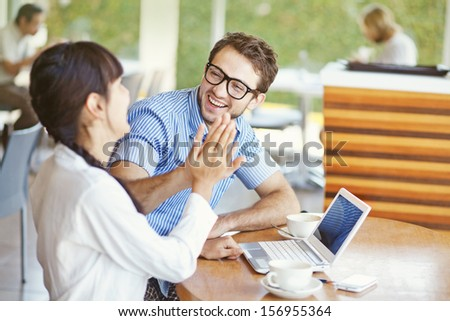 situation in office - two workers giving high five - stock photo