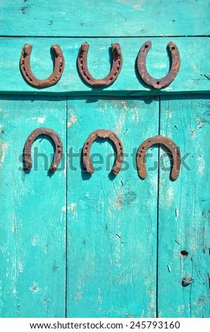 six antique rusty horseshoe on old green wooden farm barn door  - stock photo