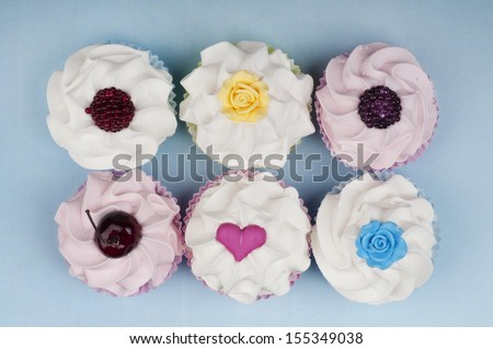 Six beautiful cupcakes shot from above with fruit, heart and rose toppings - stock photo