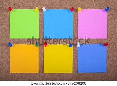 Six blank sticky notes pinned onto a noticeboard. - stock photo