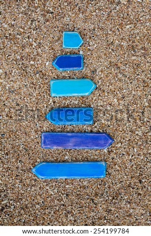 Six blue empty wooden arrows on the coral beach in Thailand. Vertical. Top view. Space for text. - stock photo