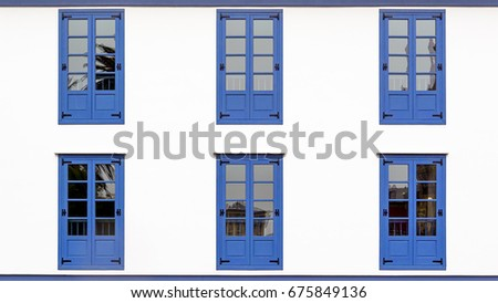 Six Blue Windows in a white facade of a building.