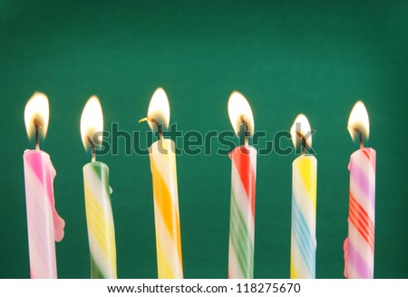 Six burning candles on green background