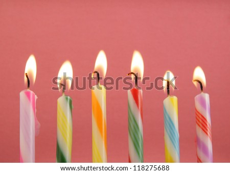 Six burning candles on pink background