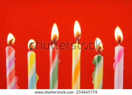 Six burning candles on red background - stock photo
