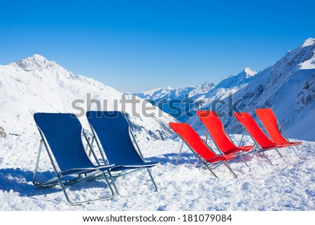 Six chairs on top of mountain range at winter season sunny day with blue sky in background - stock photo