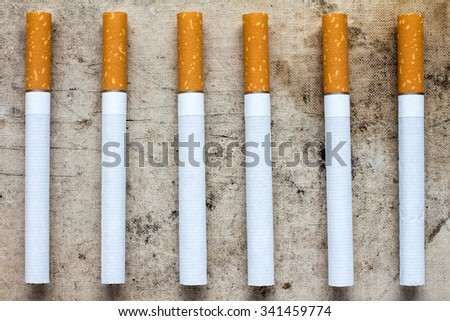 Six cigarettes with filters in a row on dirty background - stock photo