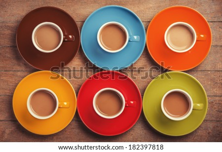 Six color cups of coffee on wooden table. - stock photo