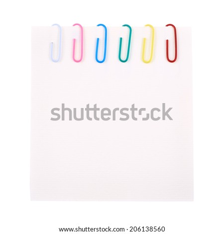 Six colorful office paper clips clipped to a square sheet of paper, isolated over the white background - stock photo