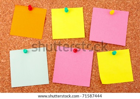 Six colorful stickers pinned to a cork board