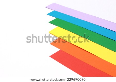 Six coloured sheets of paper stack in a rainbow order on a white background - stock photo