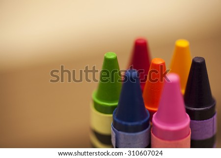 Six colourful wax crayons on a wooden background. Shot from above. Copy space to the left