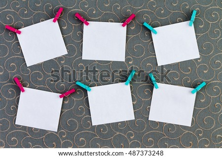 Six crooked tags with clothespins attached on top corners over cotton thread gray background