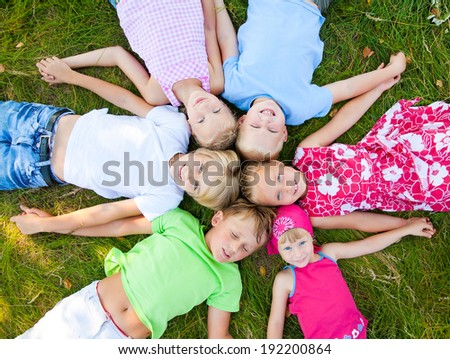 Six  cute children  lying in green grass and enjoying summertime