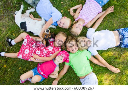 Six  cute children playing with dog  in green grass at summertime